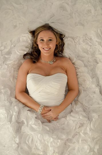 Bride laying on her back, in her wedding dress, looking up at camera. Wilmington, NC. Billy Beach.