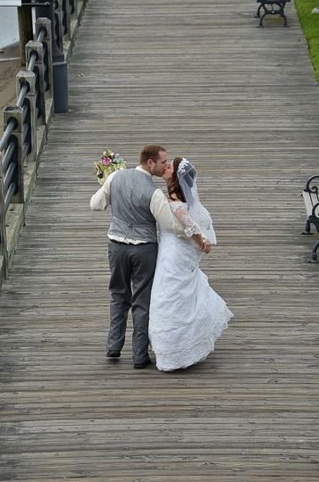 Bride and groom walking on riverwalk in downtown Wilmington NC. Shot from back. Stealing a kiss....