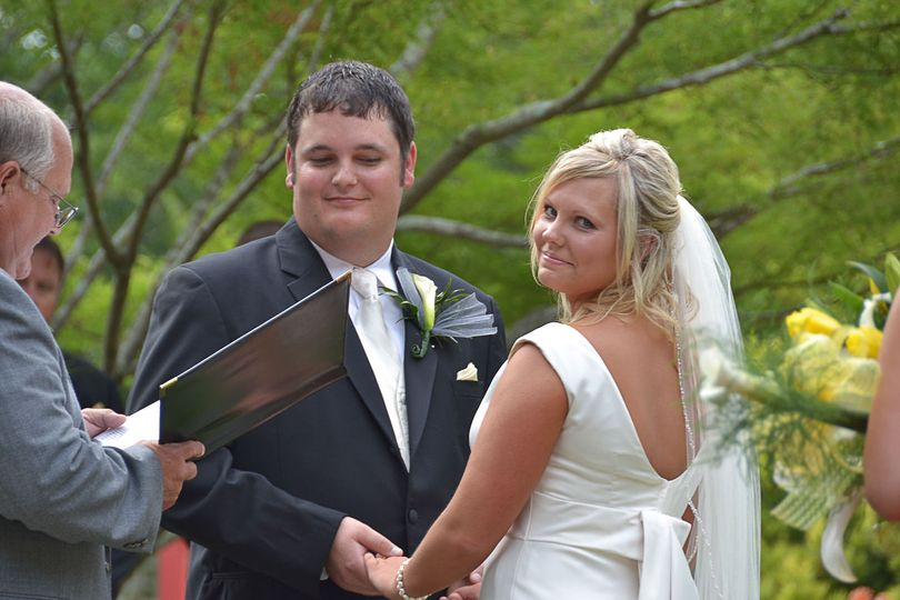 Bride and groom during wedding ceremony at the Arboretum in Wilmington, NC. Bride looking over her...