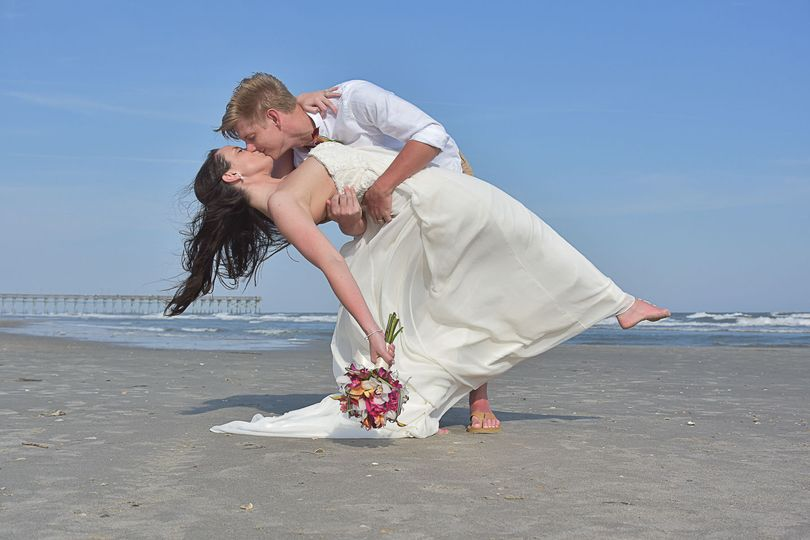 Groom dipping bride on the beach on Ocean Isle, NC. Ocean in the background, bride holding bouquet....