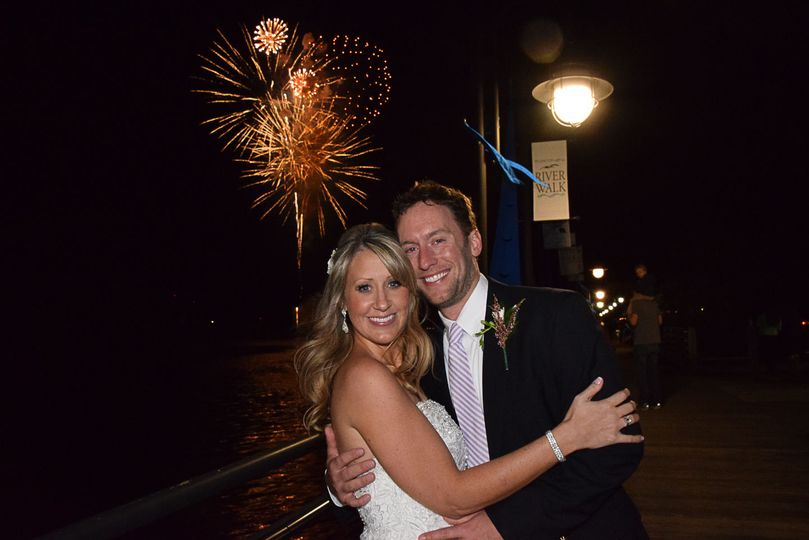 Bride and Groom on Riverwalk in downtown Wilmington, NC. Fireworks going off in the background....