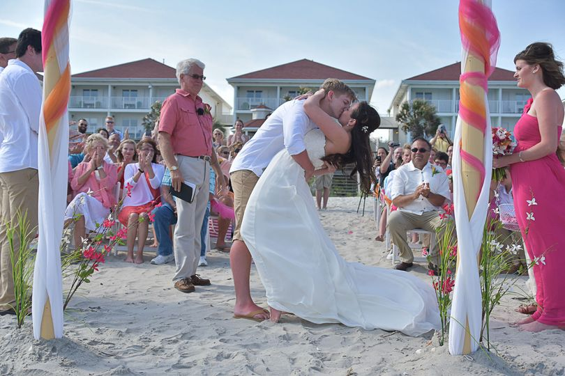 Bride and groom first kiss on the beach in Ocean Isle, NC. Shot from alter perspective. Billy Beach.
