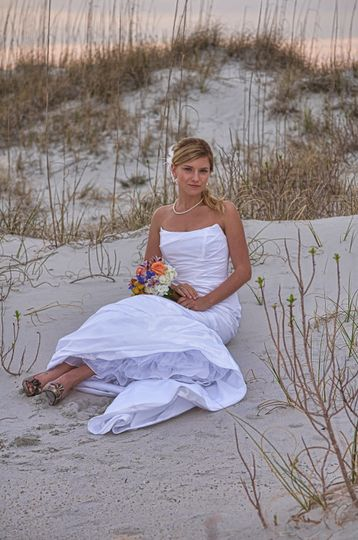 Bride sitting on dune on Wrightsville Beach, NC. Holding bouquet looking directly at camera. Billy...