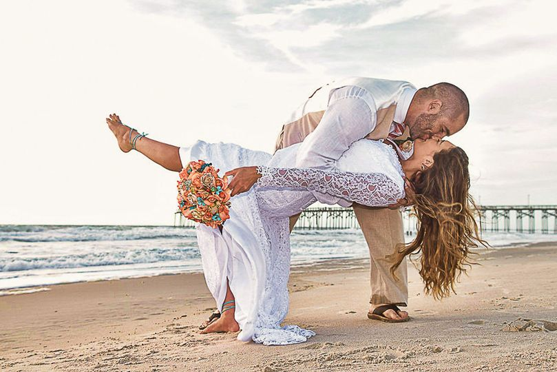 Groom dipping bride in Carolina Beach, NC. Bride holding bouquet, ocean and pier in the background.