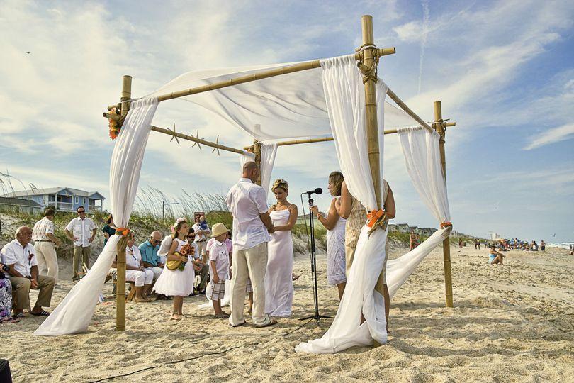 Beach wedding ceremony at Carolina Beach, NC. Dunes in the background. Billy Beach.