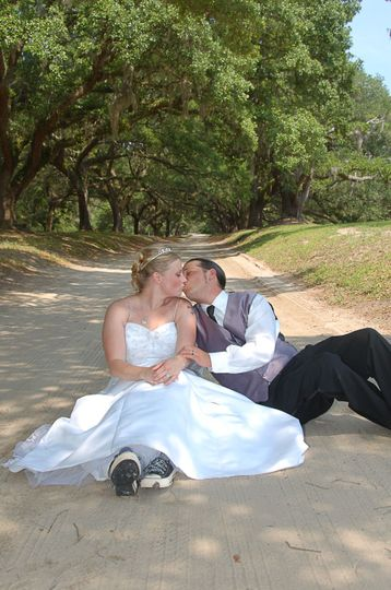 Bride and groom sharing a kiss at Orton Plantation in Brunswick County, NC. Dirt road and live oaks...