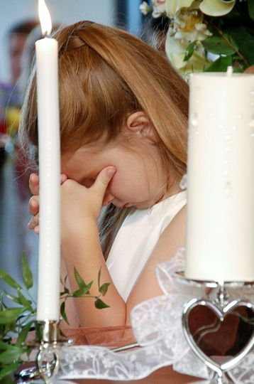 Flower girl praying during a wedding ceremony at church in Pender County, NC. Billy Beach.