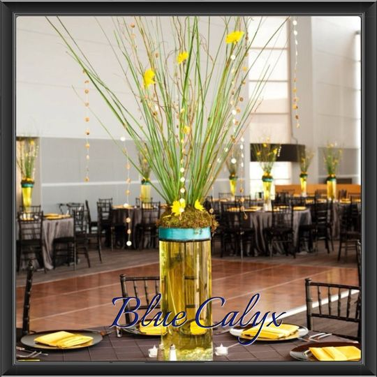 Curly Willow, tall grass and hand strung dyed shells were used in this very tall centerpiece.  The...