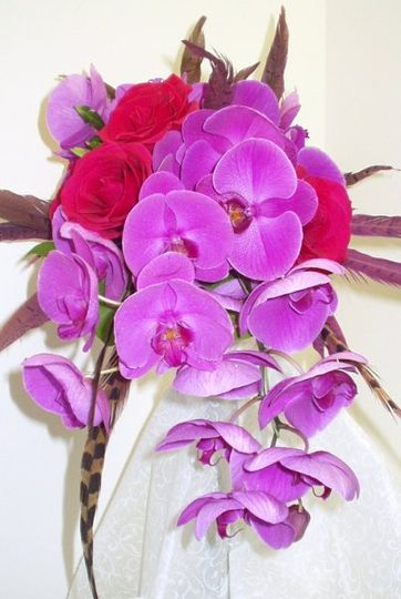 Colorful exotic bouquet with pheasant feathers, orchids and hot pink roses