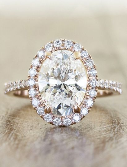 """Verity"": a halo oval diamond engagement ring with double arches on a platinum band."
