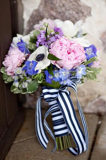 Pink, purple and white bouquet wrapped in a ribbon