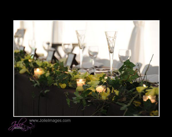 The head table at dusk.  Green ivy, rose petals & 60 votives lined the length of the table for a...