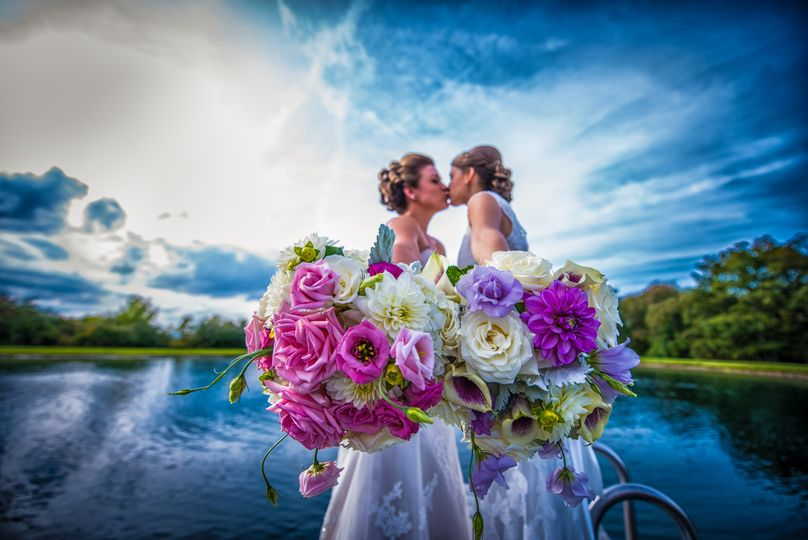 Brides kissing by the water