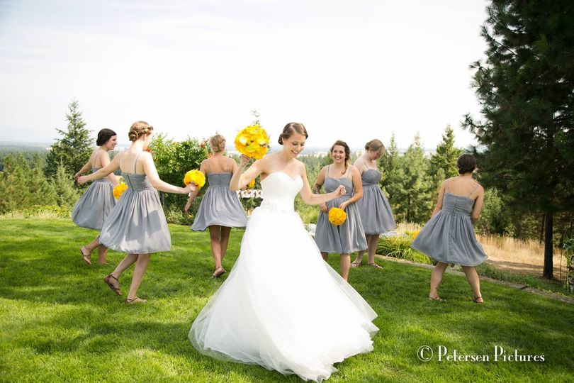 Bride and bridesmaids dancing around the grass