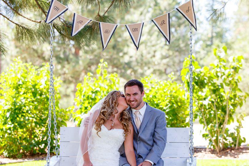 Bride kisses her groom on the swing