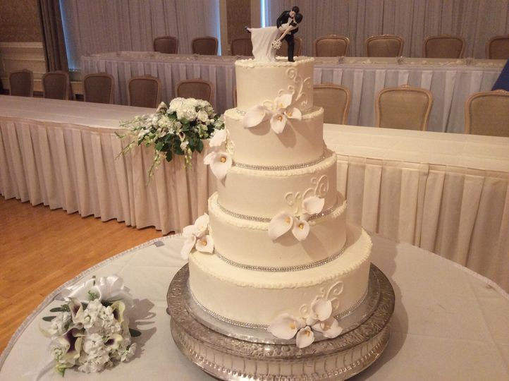 All white wedding cake with figurine on top