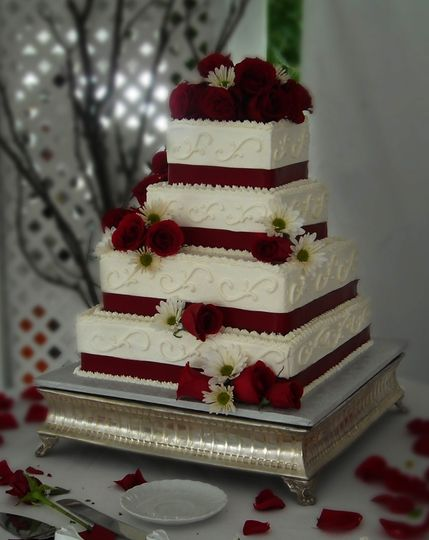 Square wedding cake with red ribbons and roses