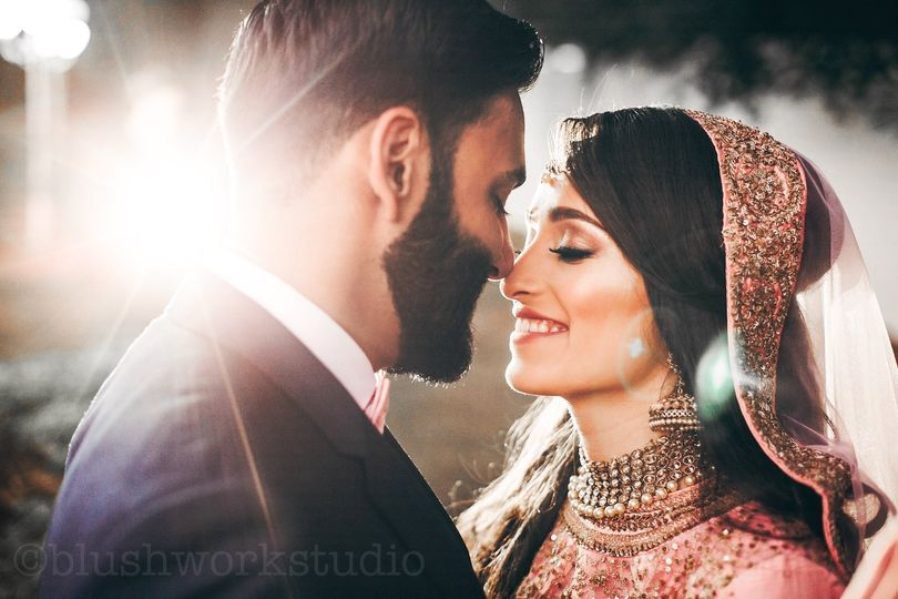 handsome bearded indian groom kisses bride in pink dress tender standing outisde 51 437070 1564281082