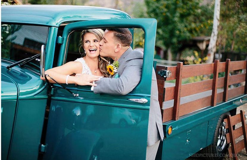 Groom kisses his bride at the truck