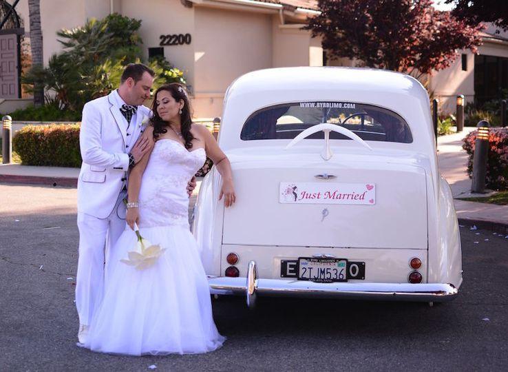 Newlyweds by the wedding car