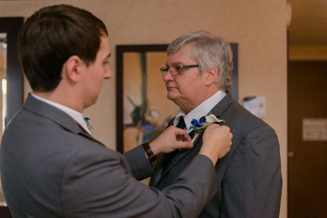 Groom putting on his father's boutonniere