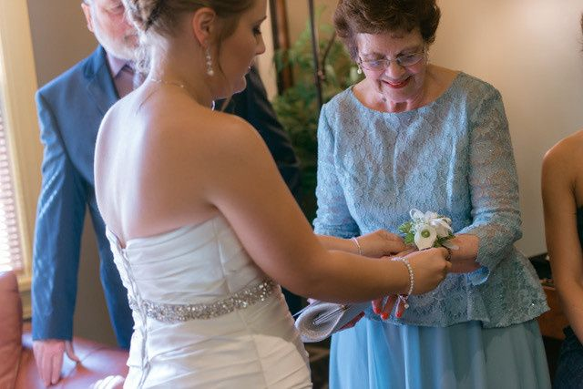 Bride putting on her mother's corsage