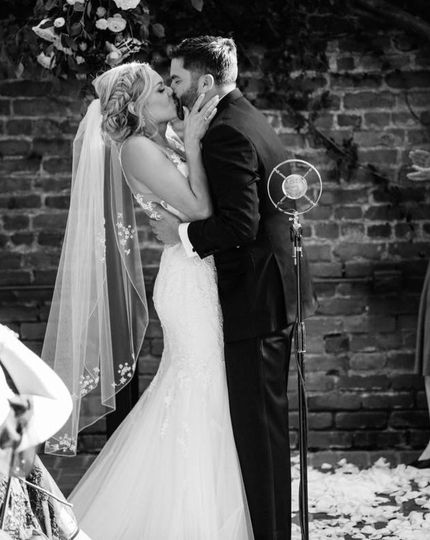 Newlyweds kiss by the mic stand