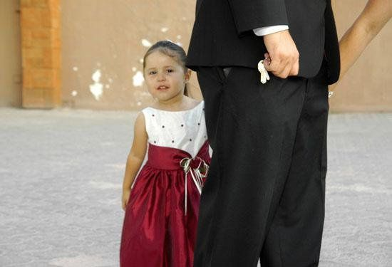 Little girl wearing a red dress arrive at the reception.