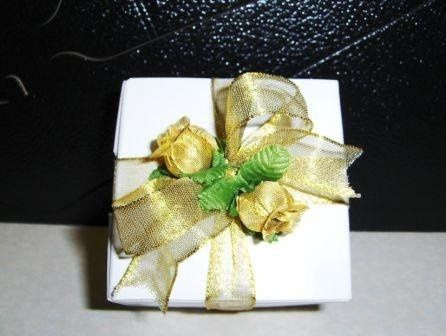 Gift wrapped in white, tied in golden ribbon and flowers