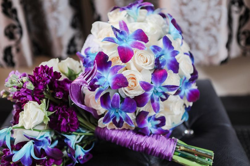 Shades of ivory, purple and blue bouquets. Orchids, roses, stock.