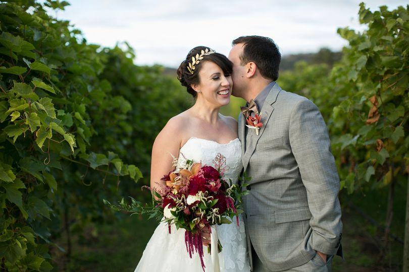 Groom kisses his bride in the field
