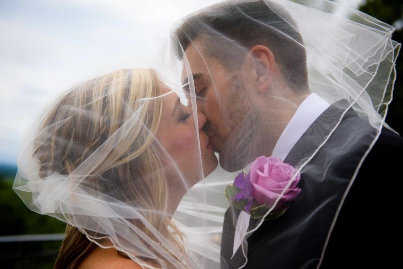 Newlyweds kissing under the veil