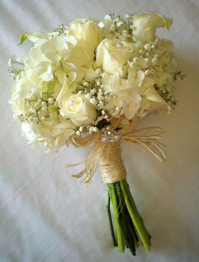 A hand-tied bouquet of creamy hydrangeas, roses, and baby breath for the bride.  Tied with twine and...