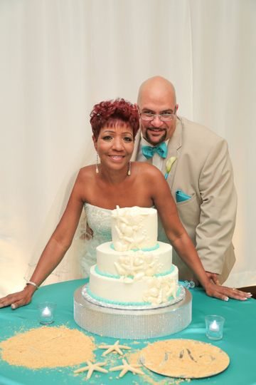 The couple posing with their wedding cake