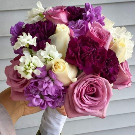 Shades of purple bridal bouquet featuring roses, stock, and carnations.