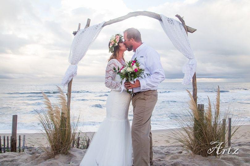 Couple kiss underneath the wedding arch