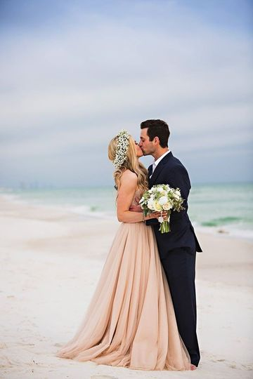 Newlyweds kiss by the beach