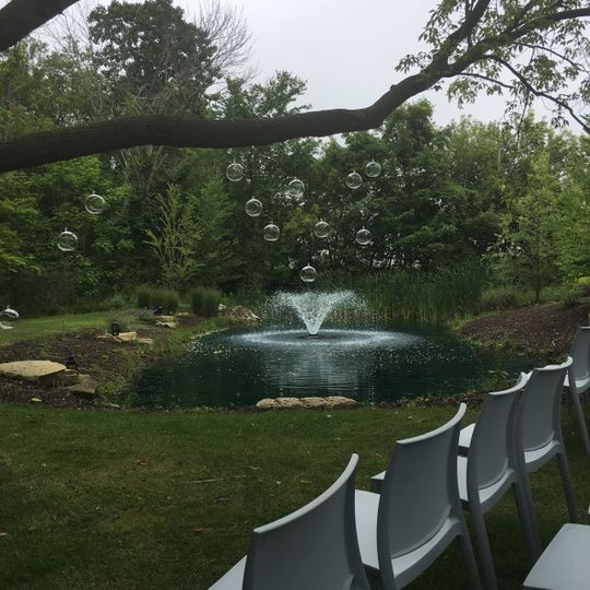 Outdoor ceremony area with garden and pond