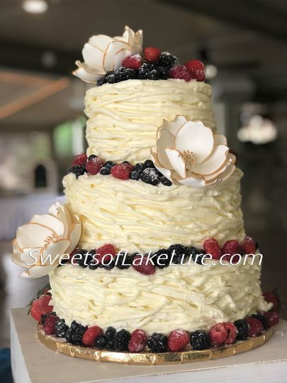 Buttercream Wedding Cake with Fresh Berries and Sugar Magnolias edged in Edible Gold