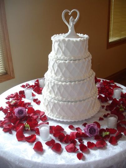 Beautiful lavender roses, dendrobium orchids and red rose petals set the scene for this cake.