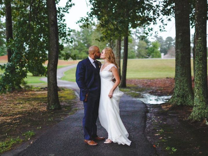 Newlyweds kiss by the winding road