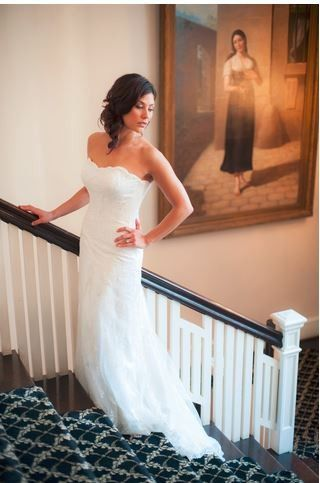 Bride on staircase leading up to second floor ballroom