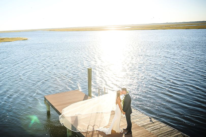 Newlyweds kissing at the dock