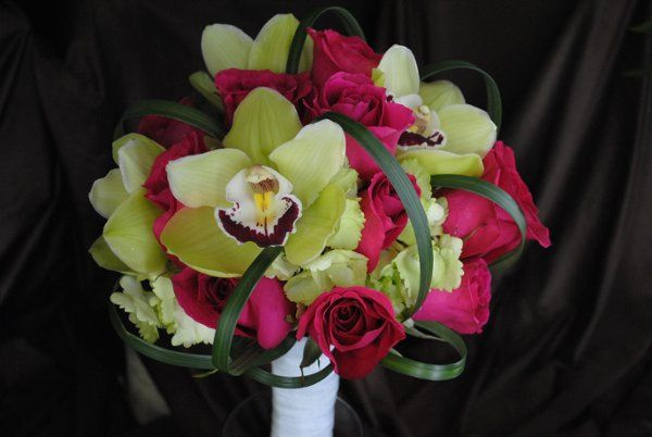 Pink roses, green hydrangea, green cymbidium orchids, and lily grass loops in a bridal bouquet