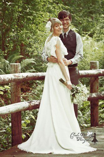 Retro style wedding photo of a newlywed couple on a bridge in the forest.