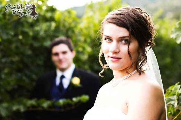 The bride is in the foreground, with the groom slightly blurred in the background, highlighting the...