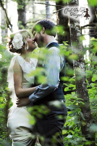 A kiss shared in the depths of the forest in this vertically oriented wedding photo, taken just...