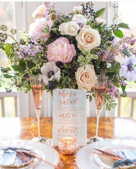 A lush centerpiece in a vintage-inspired silver mercury vase featuring peonies, anemone and sand...