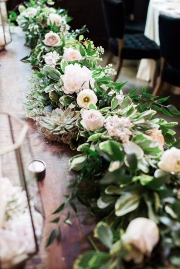Handmade garland with pops of blooms and succulents for a rectangular table centerpiece.