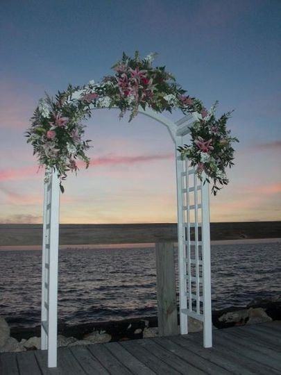 A gorgeous garden arbor filled with tropical lilies and roses made a beautiful backdrop for this...